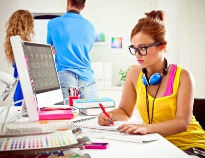 A graphic designer works in an office at her computer  pen in hand. Graphic Design Career Outlook   Industry Statistics