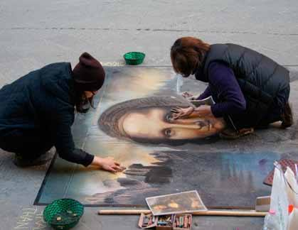 Students kneel as they create the Mona Lisa on concrete