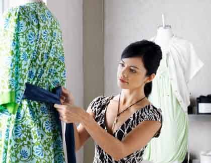 A fashion designer ties a sash on the back of dress
