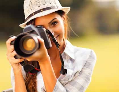 A photographer with her camera taking photos outdoors